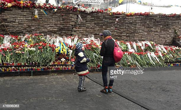 Mother and child visit the memorials to those who died in Maidan Kiev's Independence Square Thursday March 6 2014