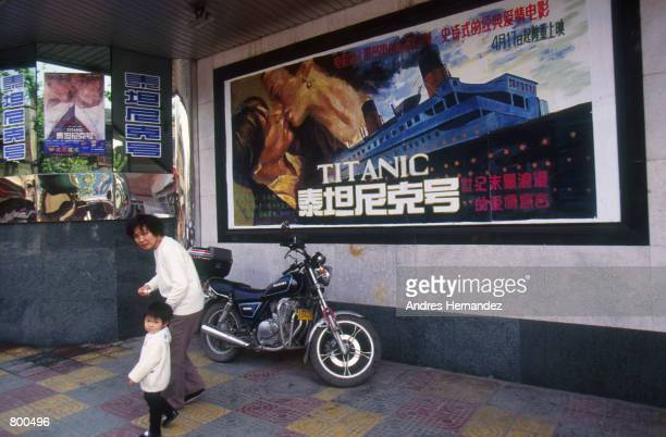 A mother and child walk pass a poster of the movie 'Titanic' May 1998 in Shanghai China Foreign influence has played a major role in Shanghai's...