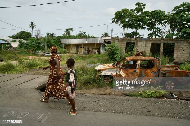 Mother and child walk past a destroyed car in a small town on the main highway on May 11,2019 near Buea in SW Cameroon. These towns were attacked by...