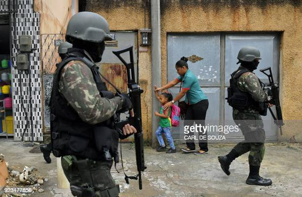 A mother and child walk past military police on patrol near the Vila Kennedy favela in Rio de Janeiro on February 23 2018 More than 3000 soldiers...