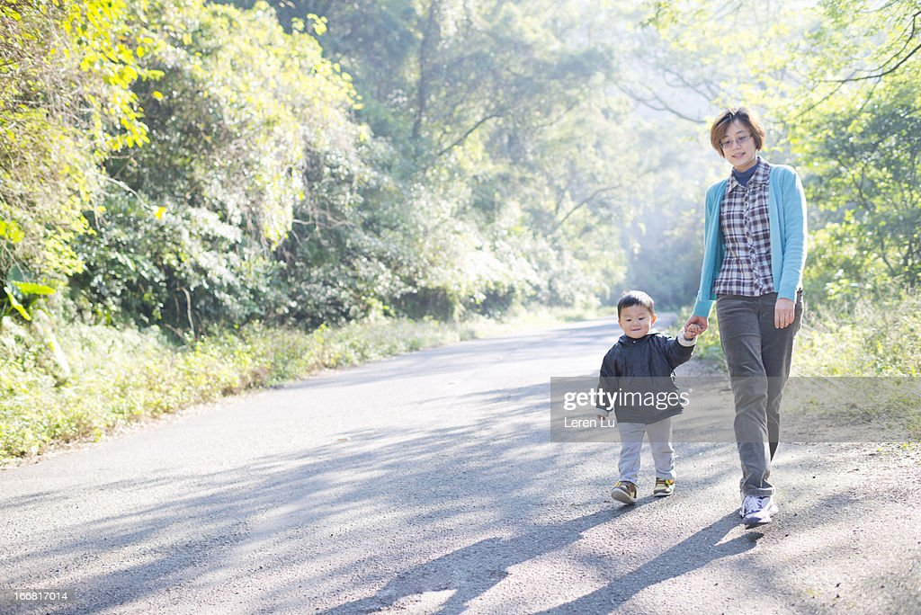 Mother and child walking on country road : ストックフォト