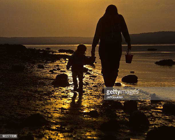 mother and child, walking on the beach at sunset - jeff goulden stock pictures, royalty-free photos & images