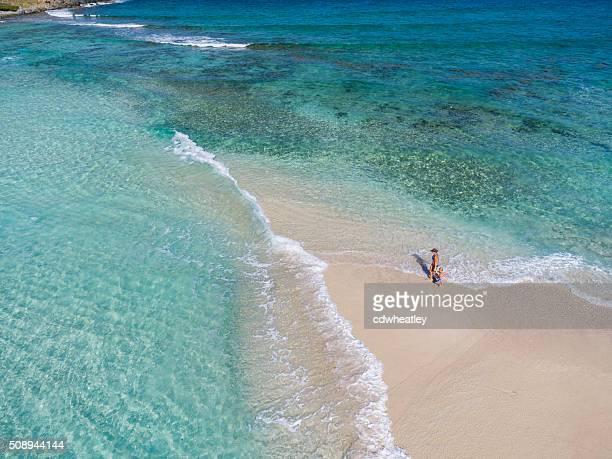 Madre e hija caminando en la playa tropical