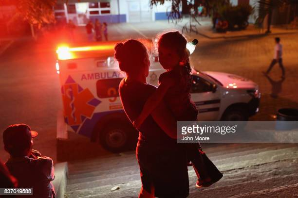 A mother and child watch as an ambulance leaves a hospital on August 17 2017 in San Pedro Sula Honduras The city has one of the highest violence and...