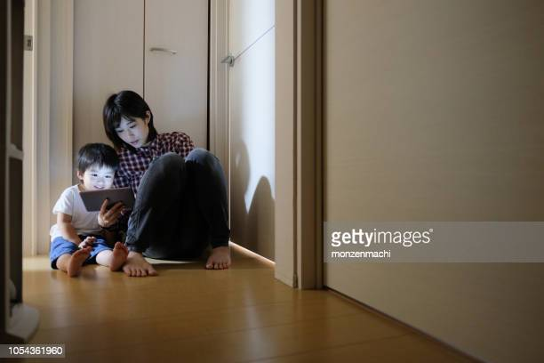 母とタブレット pc を見ている子供 - シングルマザー ストックフォトと画像