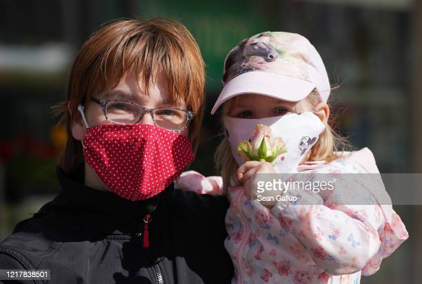 Mother and child wearing home-made protective face masks pause to allow themselves to be photographed during the coronavirus crisis on April 9, 2020...