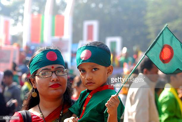 Mother and child with flag join the tribute for the freedom fighters during the 43rd Victory Day of Bangladesh in Dhaka