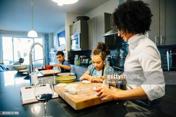 Mother and children baking in kitchen