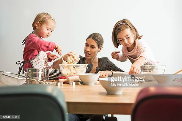 Mother and children baking, mixing batter