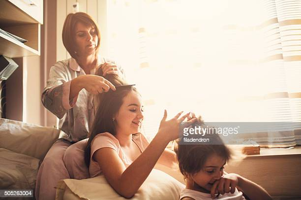 Mother and children brushing hair