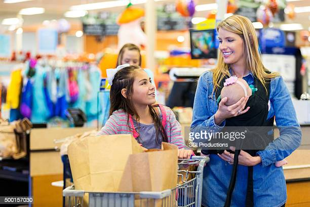 Mother and children checking out at supermarket