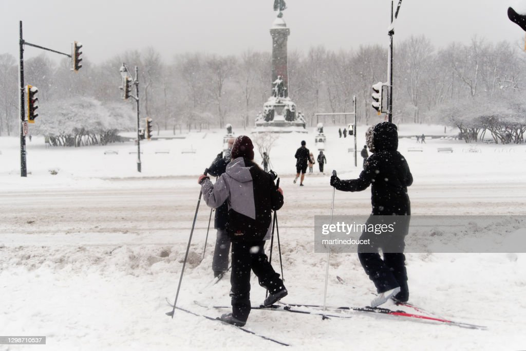Mother and children crossing street on cross-country sky in Montreal snow storm. : Stock Photo