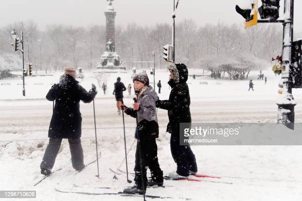 """mother and children crossing street on cross-country sky in montreal snow storm. - """"martine doucet"""" or martinedoucet stock pictures, royalty-free photos & images"""