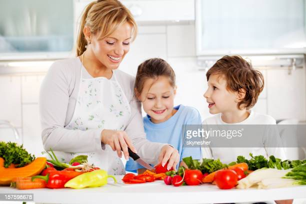 Mother and children cutting vegetables in the kitchen.