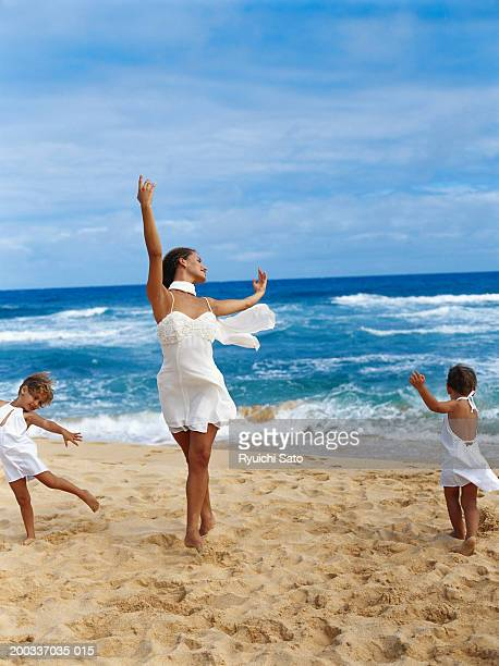Mother and children (3-4) dancing on beach, smiling