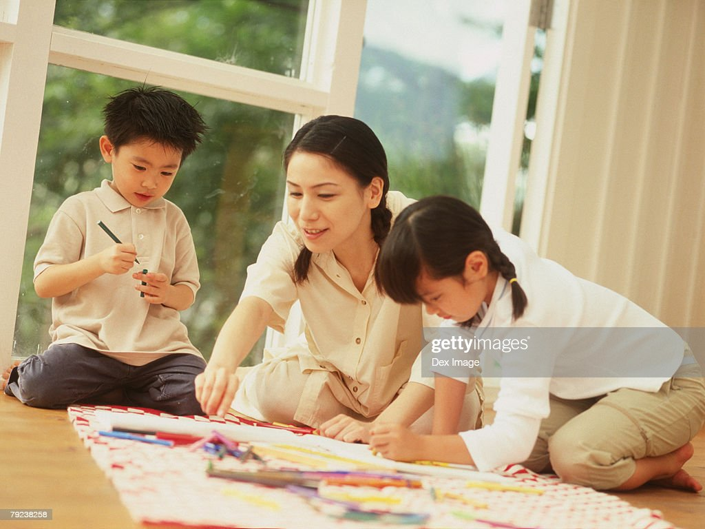Mother and children drawing using color pencils : Stock Photo