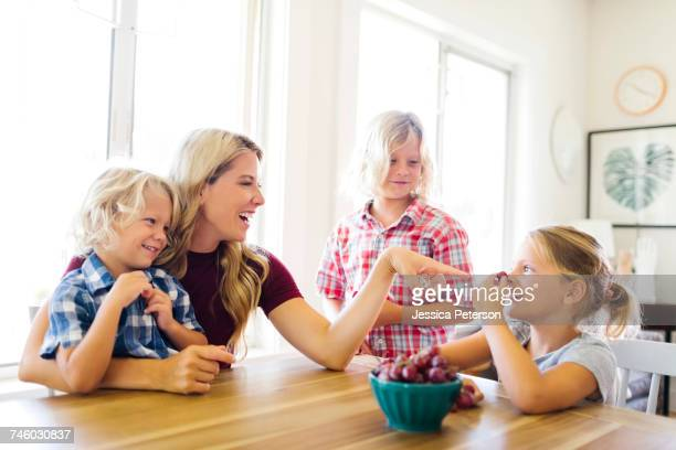 Mother and children (4-5, 6-7, 8-9) eating grapes
