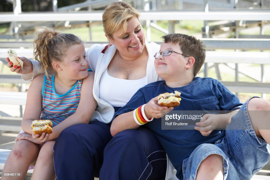 Mother and children eating sandwiches on bleachers : Foto de stock