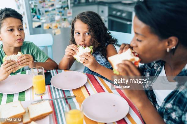 mother and children eating sandwiches - sandwich stock pictures, royalty-free photos & images