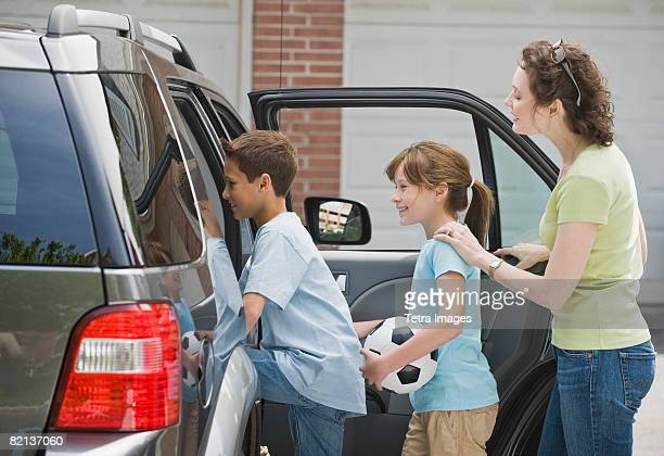 Mother and children getting into car with soccer ball
