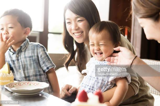mother and children happily having a snack time - affectionate stock pictures, royalty-free photos & images