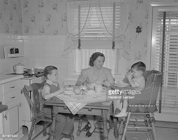 mother and children having breakfast in kitchen - {{ contactusnotification.cta }} stockfoto's en -beelden