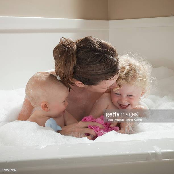 Mother and children having bubble bath