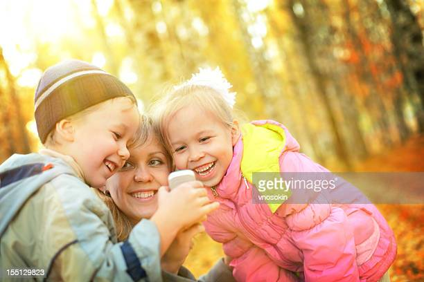Mother and children having fun in autumn park