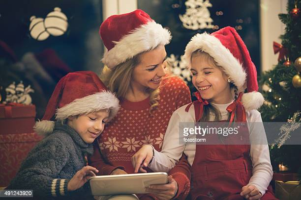 Mother and children having fun on digital tablet for Christmas