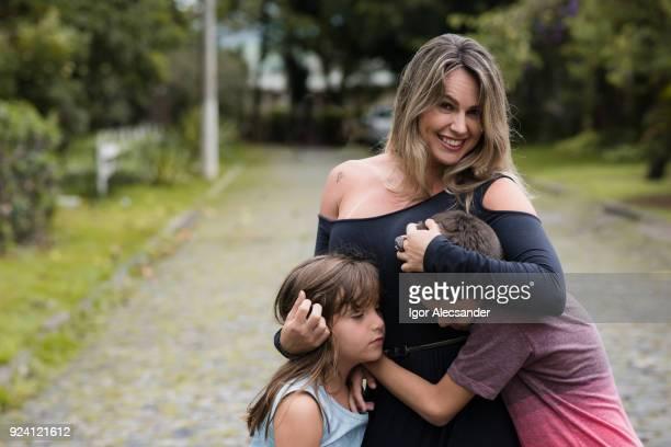 moeder en kinderen knuffelen in de straat - bewaken stockfoto's en -beelden