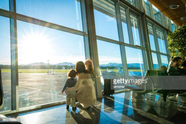 mother and children in airport - kid in airport stock pictures, royalty-free photos & images