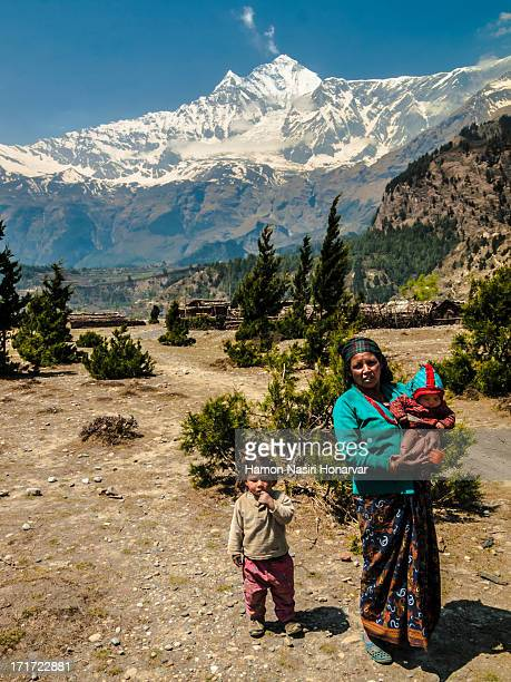Mother and children in Nepal, Annapurna Area next to Dhaulagiri 8000+ mountain in the back.