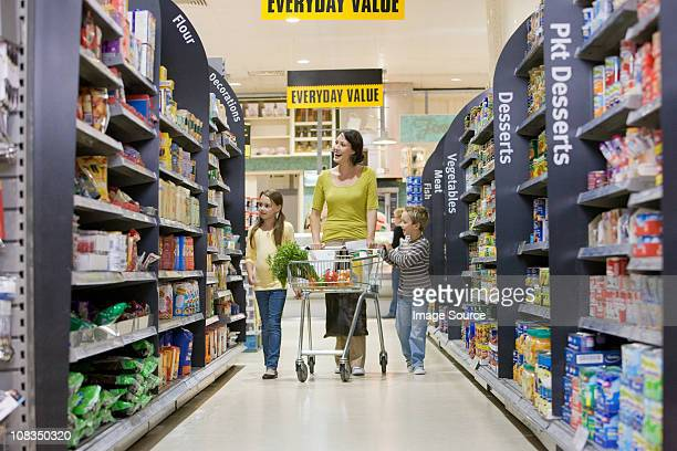 mother and children in supermarket - aisle stock pictures, royalty-free photos & images