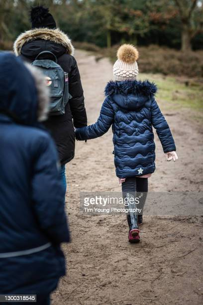 mother and children in winter clothes walking along path - warm clothing stock pictures, royalty-free photos & images
