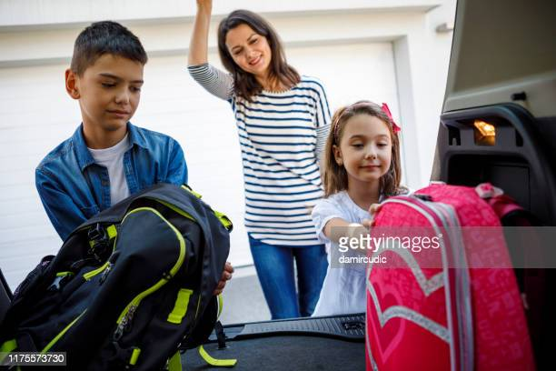 mother and children loading school backpacks into car - damircudic stock photos and pictures