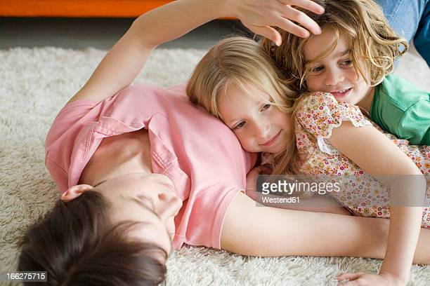 Mother and children (6-7) lying on floor in living room