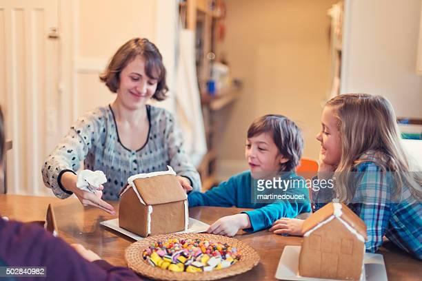 Mutter und Kinder, die ein gingerbread house wie zu Hause fühlen.