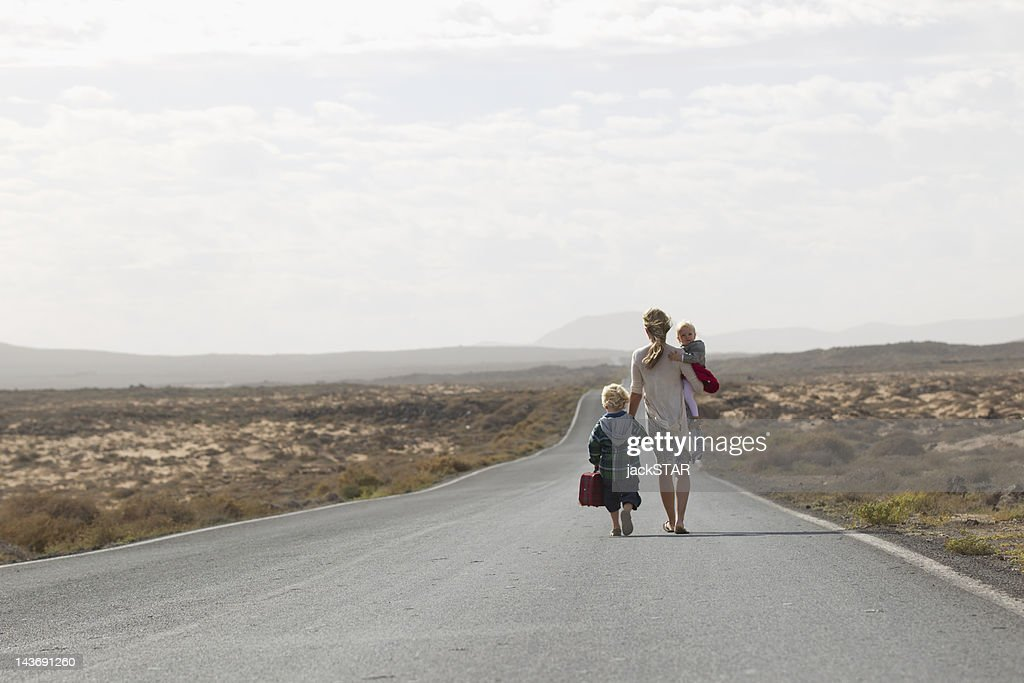 Mother and children on rural road : Stock Photo