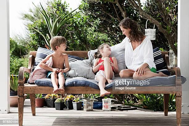Mutter und Kinder Sitzen im Freien auf