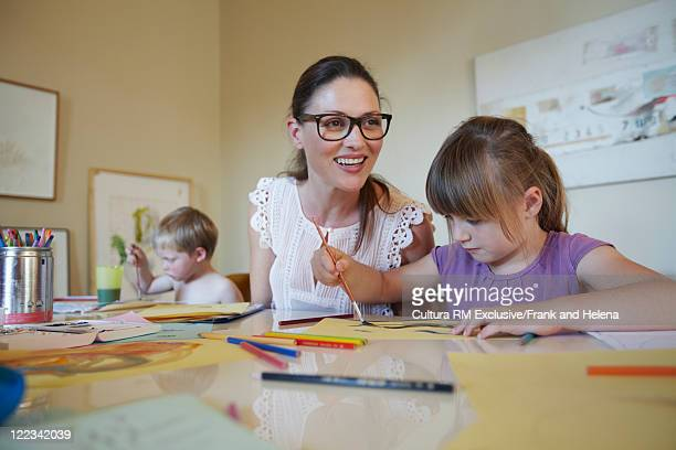 Mother and children painting together