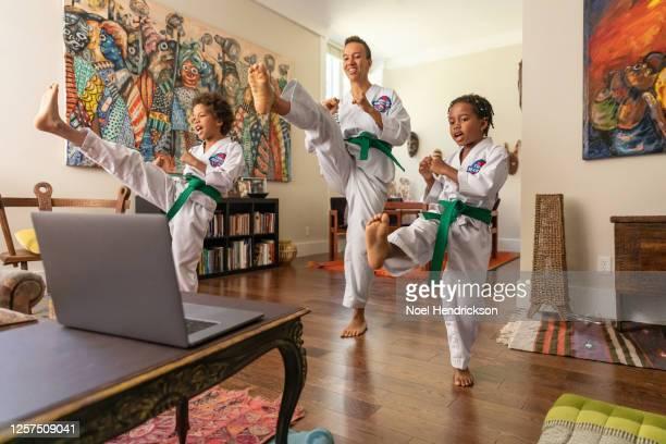mother and children performing martial arts at home - vechtsport stockfoto's en -beelden