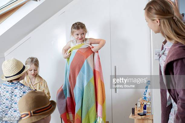 Mother and children playing dress-up in loft room