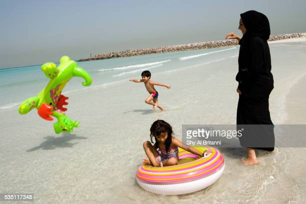 Mother and children playing on the beach.