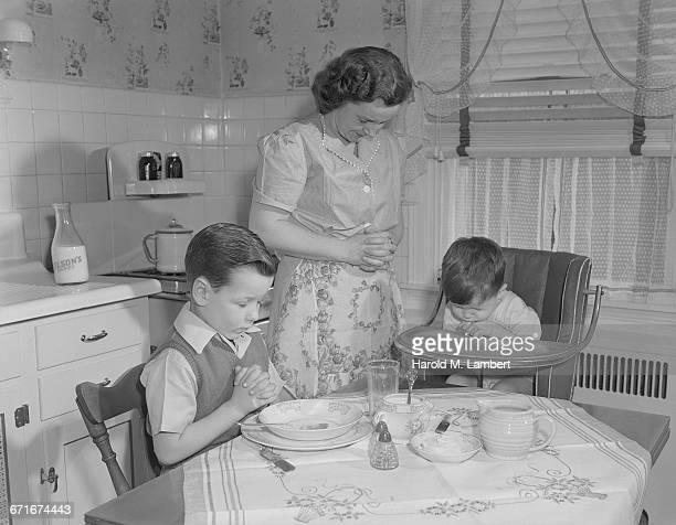 mother and children praying before breakfast - {{ contactusnotification.cta }} stockfoto's en -beelden