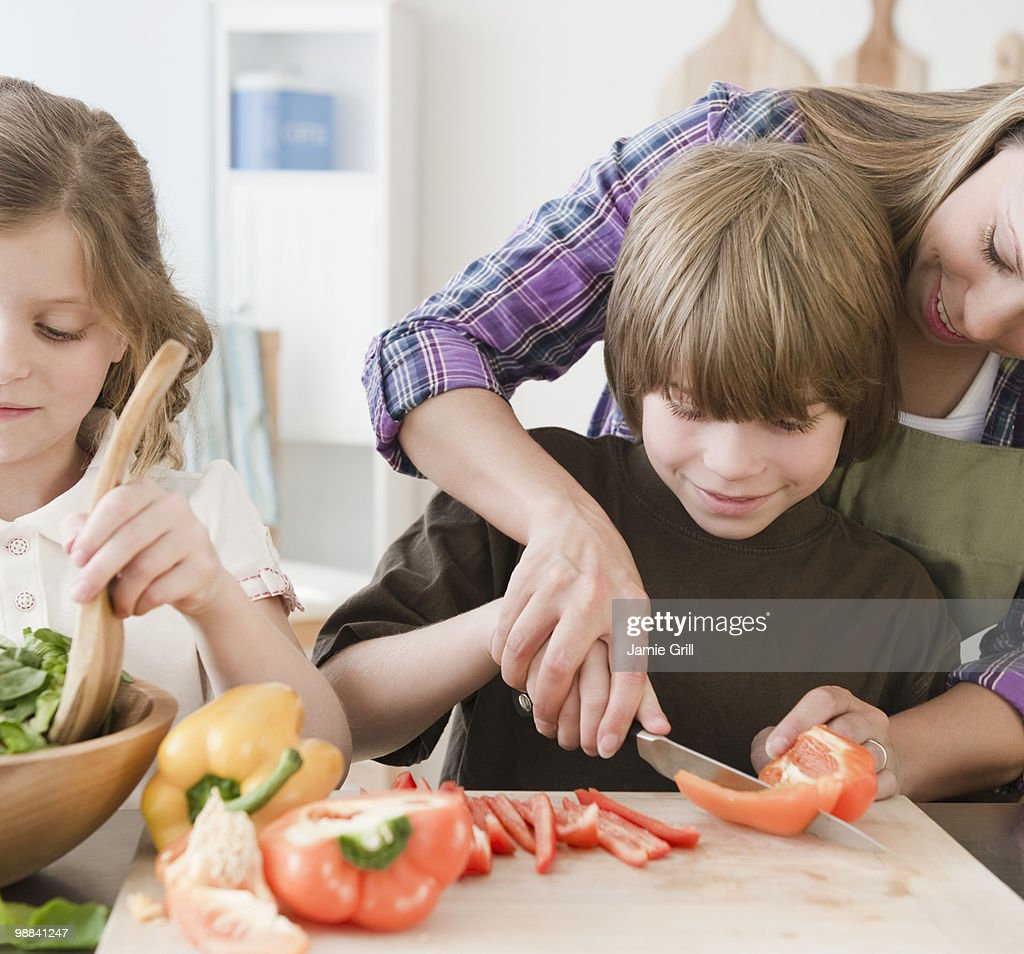 Mother and children preparing dinner together : Stock Photo