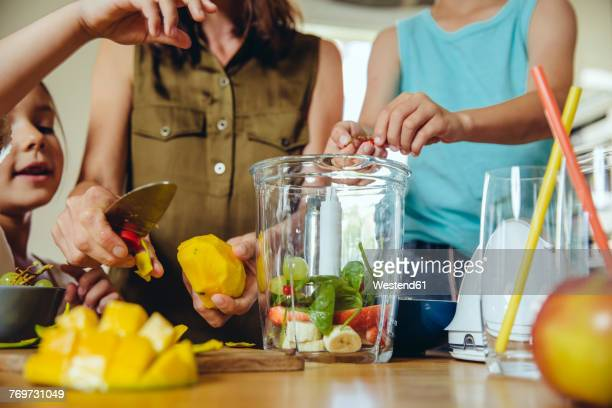 Mother and children putting fruit into a smoothie blender