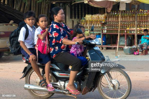 Mother and children riding a scooter in Siem Reap Cambodia