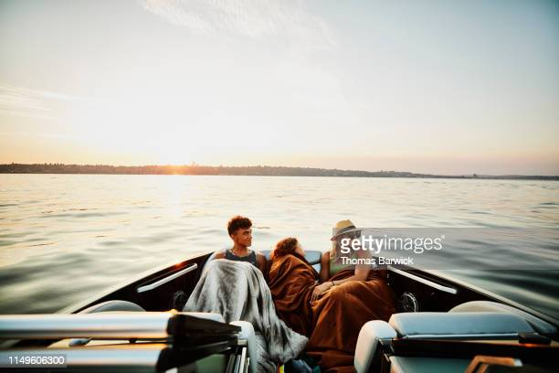 mother and children riding in bow of boat on summer evening - luxury stock pictures, royalty-free photos & images