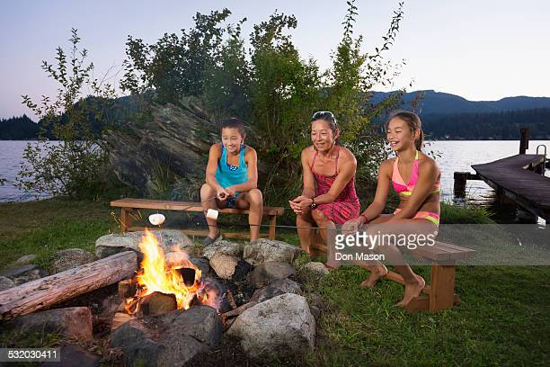 Mother and children roasting marshmallows over campfire