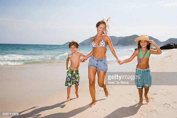 Mother and Children Running on Beach
